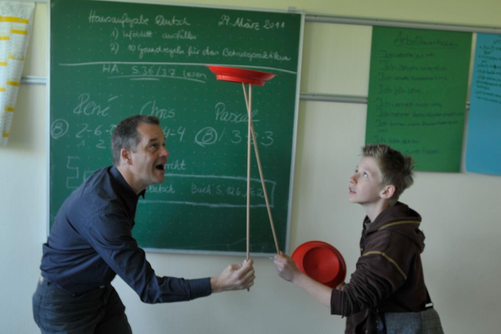 Lehrer übergibt Teller an Schüler