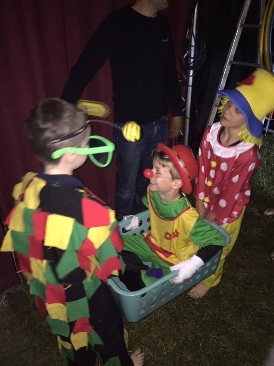 zwei Clowns tragen einen dritten im Wäschekorb